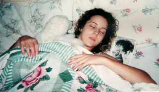 Emily, age 18, heavily medicated at home after being diagnosed with schizophrenia. She's holding a stuffed bear she found at the hospital and named Baby Bear. The small pic is her at age four long before the onset of her illness.